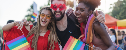 Friends stand smiling with rainbow flags